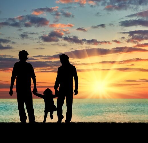 Male couple with child on beach